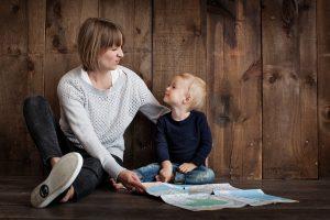 Mutter sitzt mit Kind im Arm auf dem Boden und sie schauen sich gemeinsam eine Landkarte an