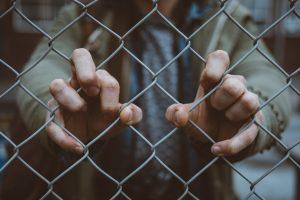 Hände umklammern Grenzzaun