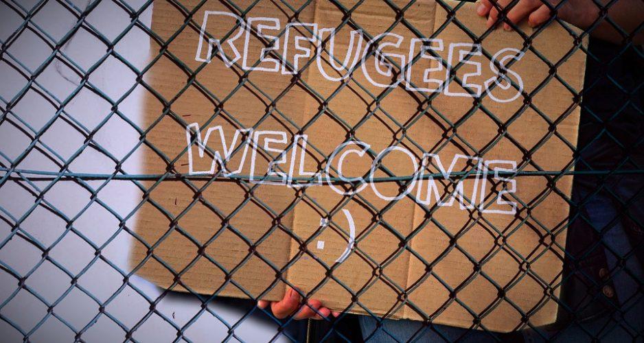 """Schild hinter Gitterzaun mit dem Schriftzug """"Refugees Welcome""""."""